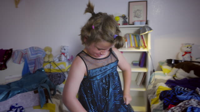 Shirtless 8 year old boy tries on a shiny blue dress - gets it on after a struggle