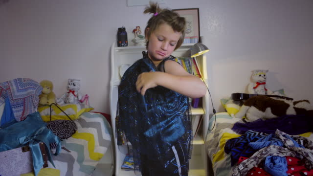 shirtless 8 year old boy tries on a shiny blue dress - struggles to put it on - only boys stock videos and b-roll footage