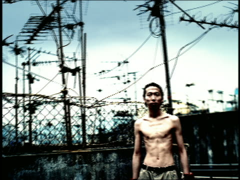 high contrast ms portrait shirtless asian man outdoors / antennae in background / hong kong - high contrast stock videos & royalty-free footage