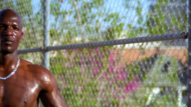 ms pan portrait shirtless bald black man looking toward camera next to chain link fence /los angeles - crisscross stock videos & royalty-free footage