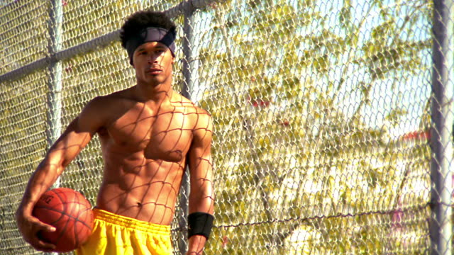 ms pan portrait shirtless black man leaning against chain link fence holding basketball /los angeles - crisscross stock videos & royalty-free footage