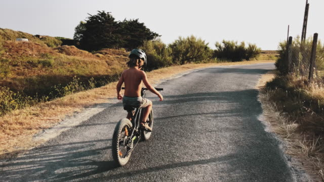 shirtless boy cycling without holding handlebars - equilibrio video stock e b–roll