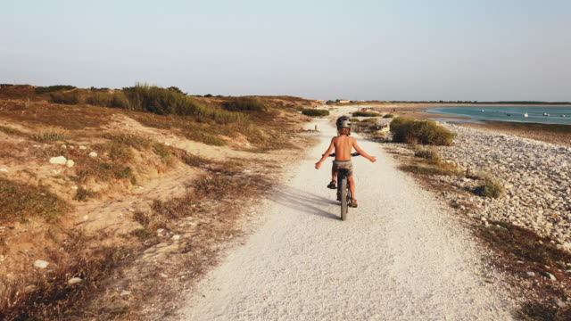 shirtless boy enjoying bicycle ride at beach - crash helmet stock videos & royalty-free footage