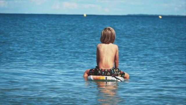 shirtless boy sitting on surfboard in ocean - surfboard stock videos & royalty-free footage
