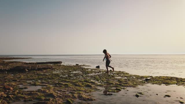 vídeos de stock e filmes b-roll de shirtless boy with fishing net walking on shore - rede de pesca objeto manufaturado