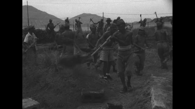 shirtless japanese prisoners run with concrete blocks on their shoulders / they dig dirt with shovels and run them to a different place / numerous... - prisoner of war stock videos & royalty-free footage