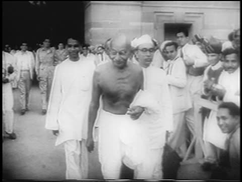 stockvideo's en b-roll-footage met shirtless mahatma gandhi walking past crowd / newsreel - mahatma gandhi