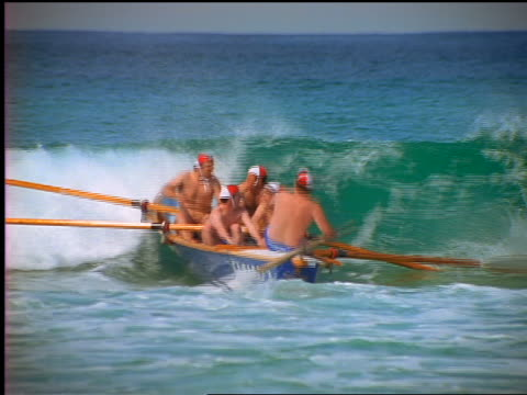 stockvideo's en b-roll-footage met shirtless male lifeguards with caps rowing small boat into wave / bondi beach, australia - badmeester