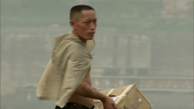 a shirtless man bundles up cardboard boxes. available in hd. - shirtless stock videos & royalty-free footage