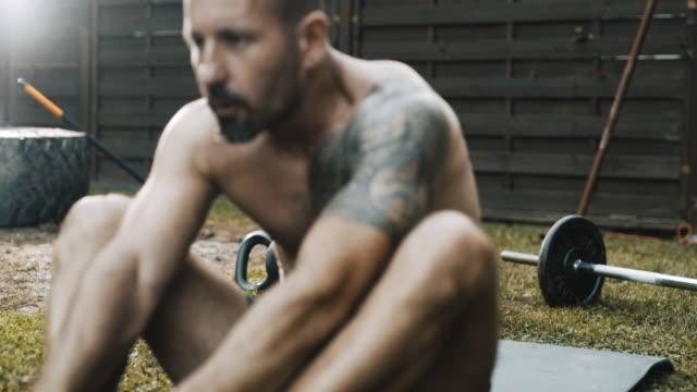 ds shirtless mann macht bauchübungen auf dem rücken - rumpfbeuge stock-videos und b-roll-filmmaterial