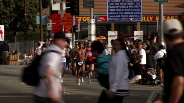 a shirtless man leads a group of marathoners as he races past spectators. - shirtless stock videos & royalty-free footage