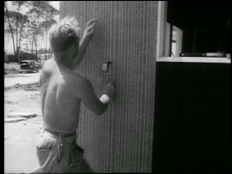 b/w 1945 rear view shirtless man nailing siding to house frame / educational - shirtless stock videos & royalty-free footage