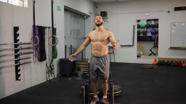 vídeos de stock e filmes b-roll de shirtless man preparing for training in gym - só homens jovens