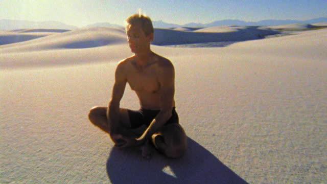 pan shirtless man sitting cross-legged meditating in desert / white sands, new mexico - cross legged stock videos and b-roll footage