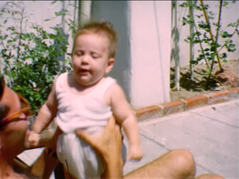 1950 home movie shirtless man sitting in chair playing with baby - single father stock videos & royalty-free footage