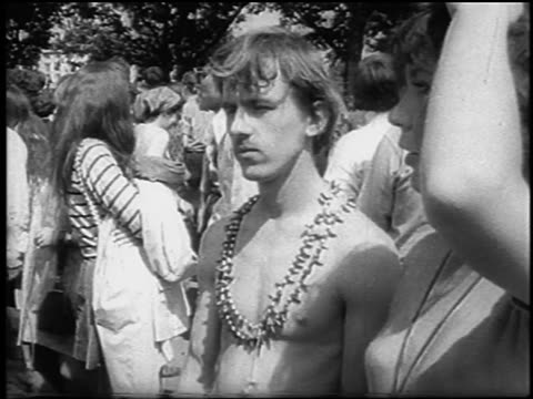 shirtless man with necklace standing in crowd at be-in / hyde park, london / newsreel - 1967 stock videos & royalty-free footage