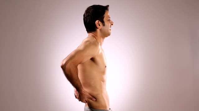 ms shirtless mid adult man rubbing his painful lower back while standing against pink background / new delhi, delhi, india - rubbing stock videos & royalty-free footage