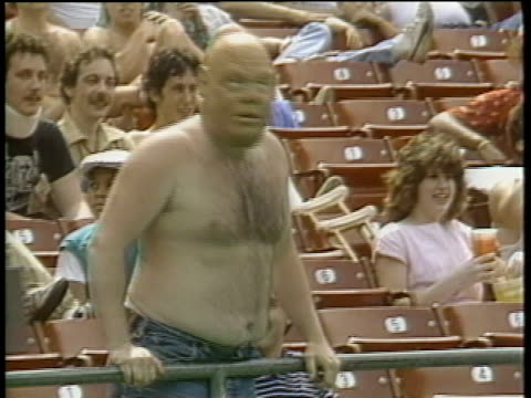 1984 MS Shirtless Pittsburgh Maulers football fan wearing scary mask and waving arms in bleachers / Pittsburgh, Pennsylvania, USA