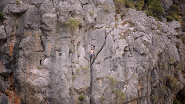 shirtless rock climber ascends sheer face - olympos, turkey - rock face stock videos & royalty-free footage