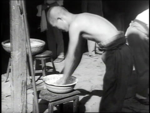 stockvideo's en b-roll-footage met 1938 ms shirtless worker washing hands and face with basin of water / japan - 1938