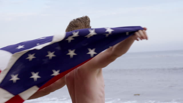 shirtless young man flying united states flag at beach 4k - vesper stock stock videos & royalty-free footage