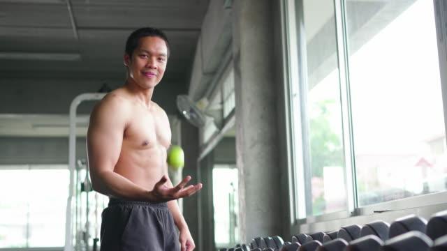 hemdloser junger mann wirft und fängt den ball im fitnessstudio - halbbekleidet stock-videos und b-roll-filmmaterial