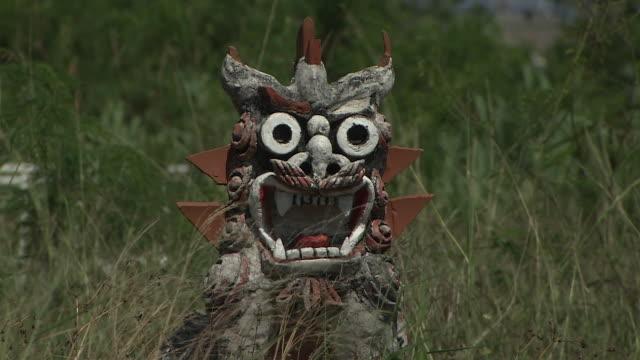 shisa in the grass in miyako island, okinawa, japan - mythologie stock-videos und b-roll-filmmaterial