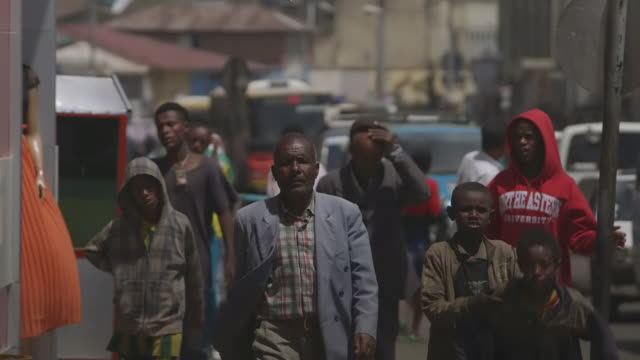 ms sho tof pedestrians and heavily laden cart packed with sacks tries to navigate through traffic whilst man / addis abbaba, ethiopia - アジスアベバ点の映像素材/bロール