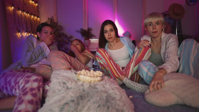 shocked girlfriends at sleepover eating popcorns and watching a horror movie on a tv - slumber party stock videos & royalty-free footage