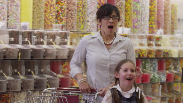 shocked mother covering daughters eyes in candy store / highland, utah, united states,  - gereiztheit stock-videos und b-roll-filmmaterial
