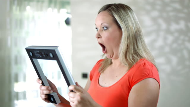 hd dolly: shocked woman looking at bathroom scale - dieting stock videos and b-roll footage