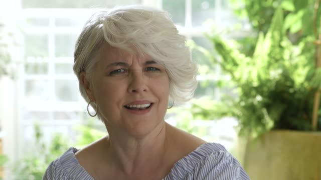 shocked woman with short hair looking towards camera. - kopf schütteln stock-videos und b-roll-filmmaterial