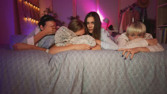 shocked young girlfriends at sleepover watching a horror movie on a tv - slumber party stock videos & royalty-free footage
