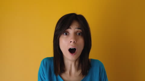 shocked young woman looking at camera on yellow background - surprise stock videos & royalty-free footage