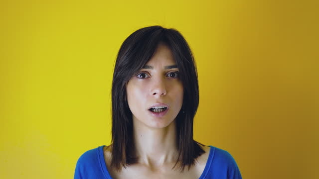 Shocked young woman looking at camera on yellow background