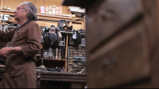 la shoe cobbler repairing shoes at workbench / santa monica, california, united states - letterbox format stock videos and b-roll footage