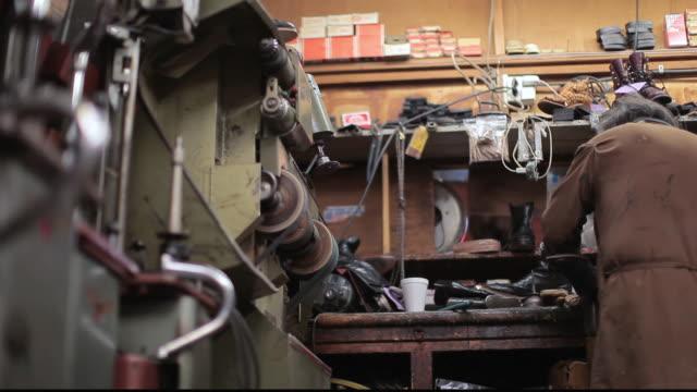 stockvideo's en b-roll-footage met la shoe cobbler repairing shoes at workbench / santa monica, california, united states - breedbeeldformaat