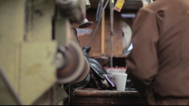 stockvideo's en b-roll-footage met ms shoe cobbler sanding sole of a shoe / santa monica, california, united states - breedbeeldformaat