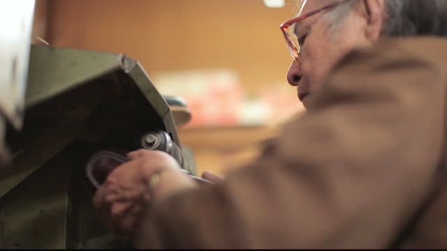 stockvideo's en b-roll-footage met cu shoe cobbler sanding the sole of a shoe / santa monica, california, united states - breedbeeldformaat
