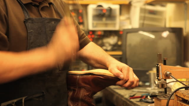 MS Shoe maker attaching new sole onto cowboy boot in workshop / Lebanon, New Hampshire, USA / AUDIO