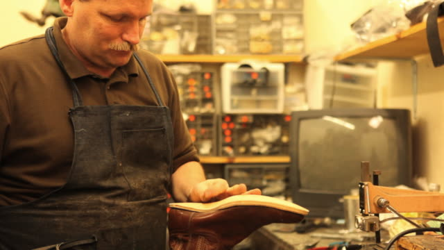 MS ZO Shoe maker attaching new sole onto cowboy boot in workshop / Lebanon, New Hampshire, USA / AUDIO
