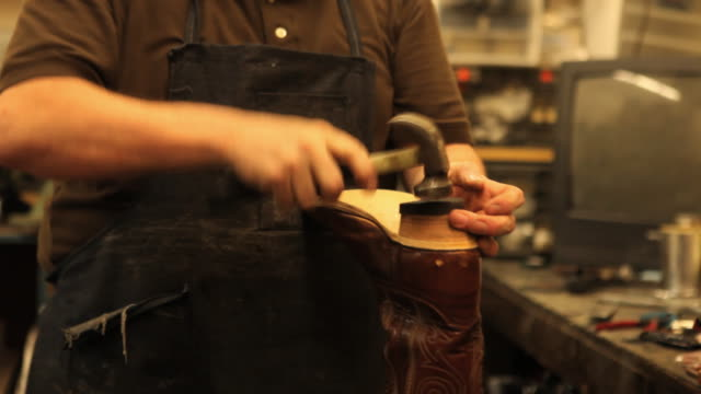 MS TU ZO Shoe maker attaching new sole onto cowboy boot in workshop / Lebanon, New Hampshire, USA / AUDIO