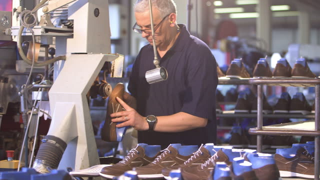 shoe production, man abrades the leather upper and put the shoe on a table down - leather shoe stock videos and b-roll footage