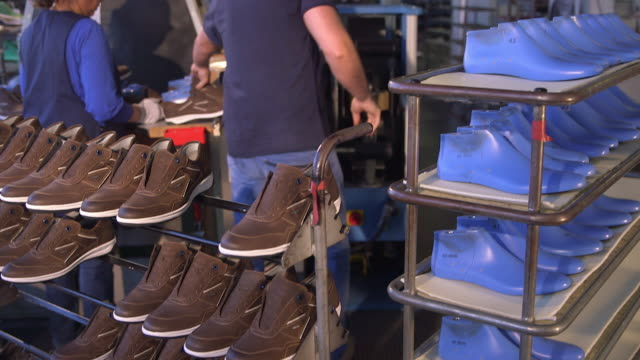 shoe production, man put the final shoes and the shoe last in a rack down - shoes in a row stock videos & royalty-free footage