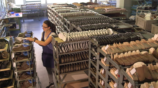shoe  production, woman, chooses soles in the right sizes in a warehouse, from above - shoes in a row stock videos & royalty-free footage