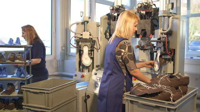 vídeos y material grabado en eventos de stock de shoe production, woman standing on a machine with leather upper - calzado