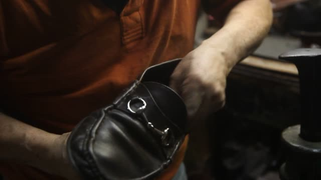 A shoe repair professional works on a badly damaged loafer in the basement of Jim's Shoe Repair Shop on 59th Street in New York NY The employee...