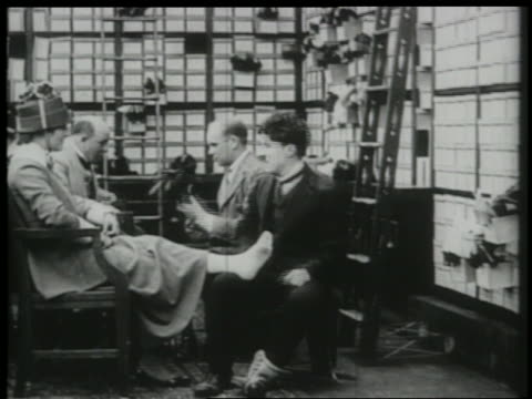 b/w 1916 shoe salesman charlie chaplin tickles woman's feet pushes man takes shoes from shelf - 1916 stock videos & royalty-free footage