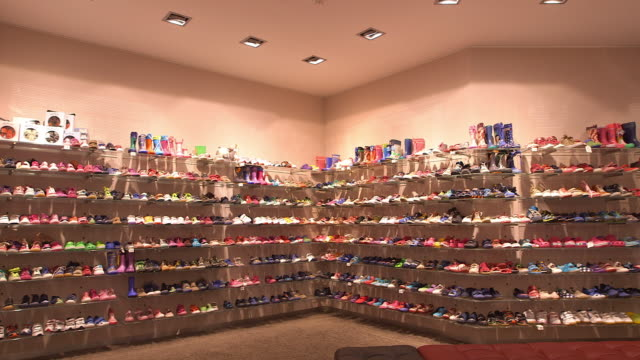 shoe shop, childâ´s shoes in a rack, pan shot, wide - scarpe da ginnastica video stock e b–roll