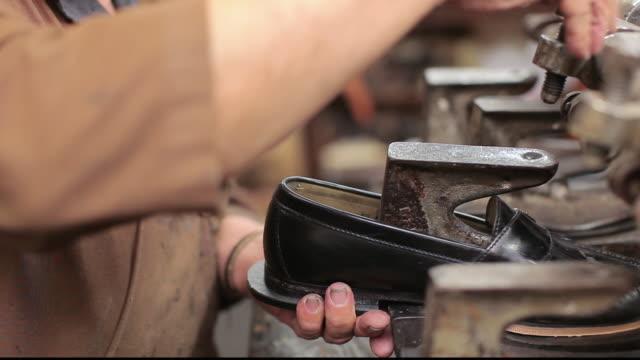 CU Shoemaker repairing a shoe in his shop / Santa Monica, California, United States